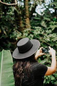 眼鏡をかけて黒い帽子をかぶった携帯電話を使用している女性の肖像画。