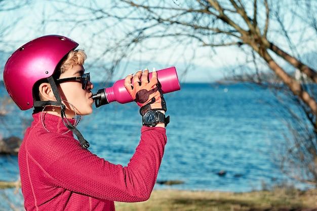 自転車のヘルメットをかぶって水を飲み、湖の近くの自然公園で休んでいる女性の肖像画