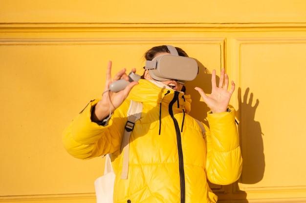 따뜻한 옷을 입고 겨울에 밝은 햇빛에 노란색 벽에 거리에서 가상 현실 안경을 착용하는 여자의 초상화