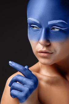 Портрет позирующей женщины покрыт синей краской