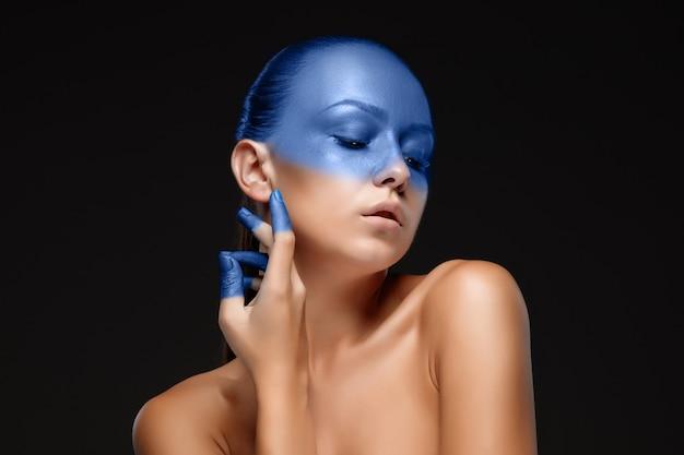 파란색 페인트로 덮여 포즈를 취하는 여자의 초상화
