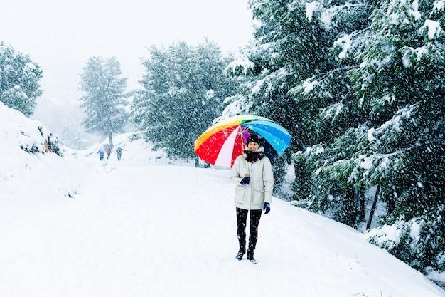 산 풍경에 걷는 다채로운 우산을 가진 여자의 초상화.