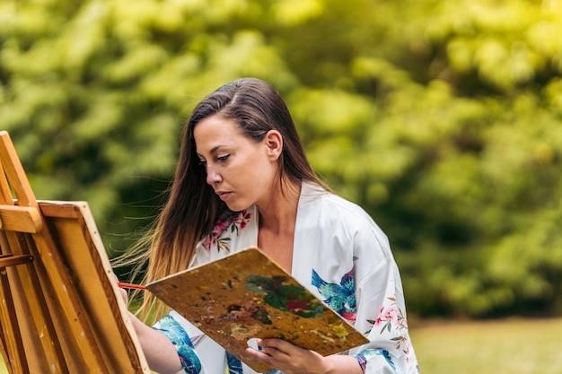 공원에서 캔버스에 집중된 표정 그림을 가진 여성의 초상화.