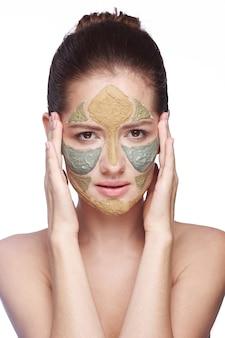 그녀의 얼굴에 화장품 미용 마스크를 가진 여자의 초상화