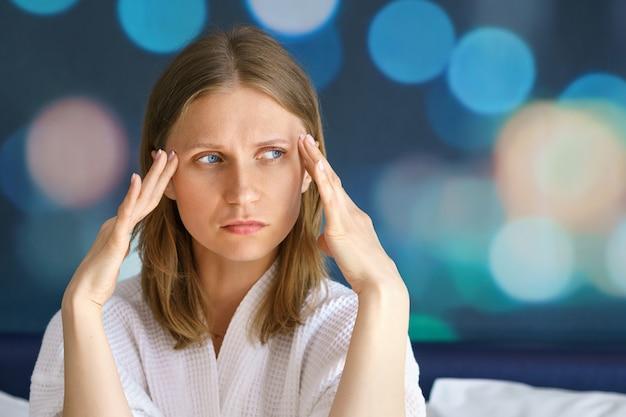 Портрет женщины с головной болью, держащей руки у висков