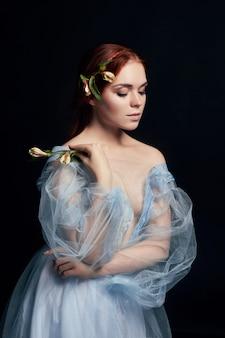 책 표지에 중세 꽃을 손에 들고 있는 여성의 초상화. 긴 머리를 가진 소녀의 완벽한 자연미