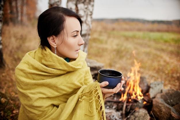 森のキャンプファイヤーで秋の熱いお茶のマグカップを持つ女性の肖像画。秋の森でのピクニック。森の焚き火で暖められた毛布に包まれた少女