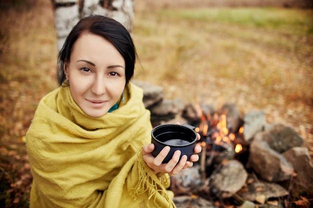 숲 모닥불에서 가을 손에 뜨거운 차 한 잔을 들고 있는 여성의 초상화. 가을 숲에서 피크닉입니다. 숲 모닥불에 데워진 담요에 싸인 소녀