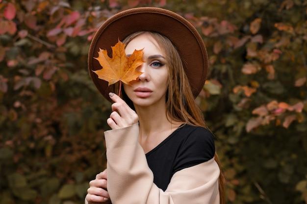 Портрет женщины с осенним макияжем и осенним листом. крупный план