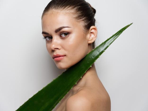 Портрет женщины с открытыми плечами и зеленым листом алоэ косметологический макияж чистой кожи