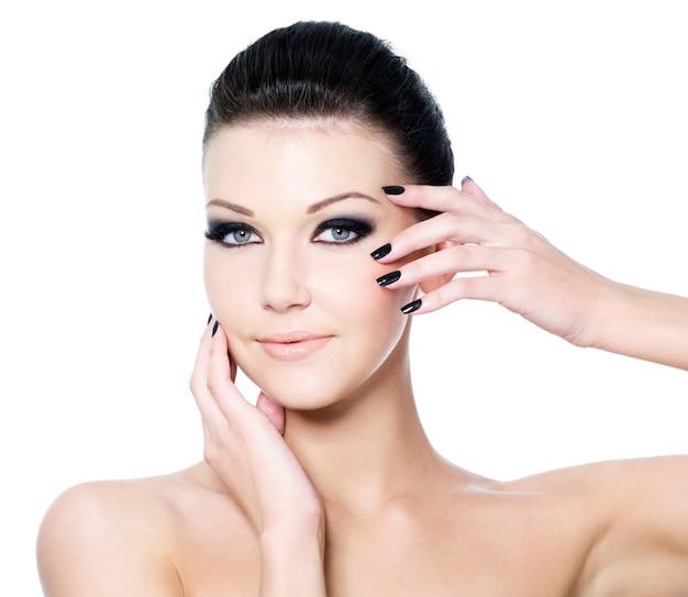 아름다운 검은 눈 화장과 미용 매니큐어를 가진 여자의 초상화
