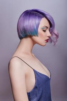 밝은 색의 날아다니는 머리, 모든 색조의 보라색을 가진 여성의 초상화. 헤어 컬러링, 아름다운 입술과 메이크업. 바람에 나부끼는 머리카락. 짧은 머리를 가진 섹시 한 소녀입니다. 전문적인 착색