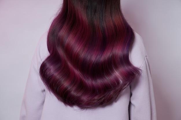 Портрет женщины с яркими развевающимися волосами всех оттенков фиолетового. блестящие здоровые окрашенные волосы, красивые губы и макияж