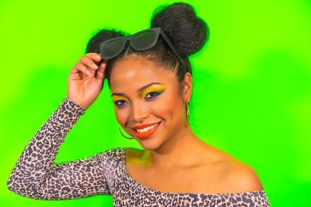 Портрет женщины с ярким макияжем и прической с двумя боковыми пучками в стильных солнцезащитных очках