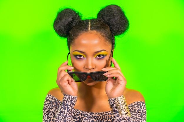 Портрет женщины с ярким макияжем и прической с двумя боковыми пучками, позирующей на зеленом