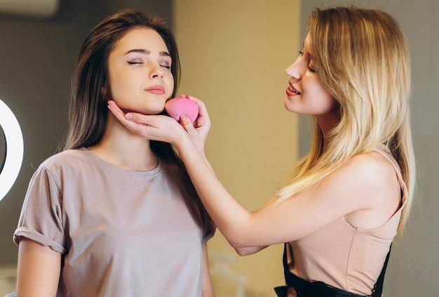 갈색 머리에 눈을 감고 컨실러를 바르고 있는 여성의 초상화. 얼굴에 가까운 핑크 뷰티 블렌더.