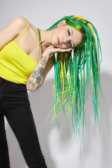 녹색과 노란색 색상의 창의적으로 색깔의 머리를 가진 여자의 초상화. 다채로운 밝은 향취, 아름다운 현대 메이크업