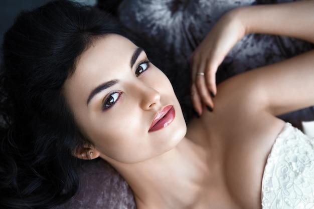 Портрет женщины с темными волосами на серой стене