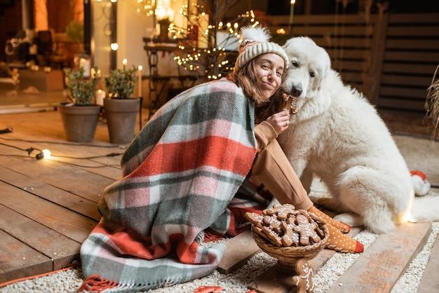 年末年始を祝って、一緒に座って、自宅の美しく装飾されたテラスでジンジャーブレッドを食べている彼女のかわいい犬と一緒に女性の肖像画