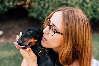Portrait of a woman with her dog sticking out tongue
