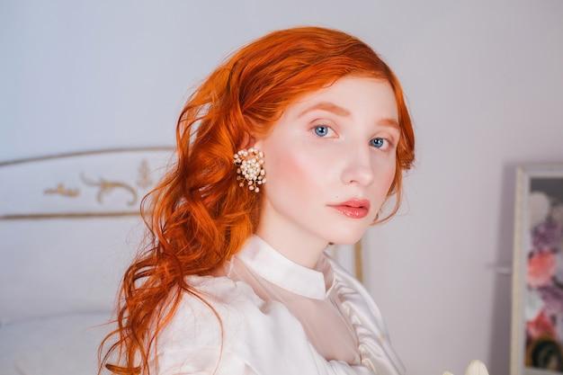 彼女の耳に白い真珠のイヤリングと白いヴィンテージのウェディングドレスに長い赤い巻き毛を持つ女性の肖像画。淡い肌、青い目、寝室の明るく珍しい外観の赤い髪の少女