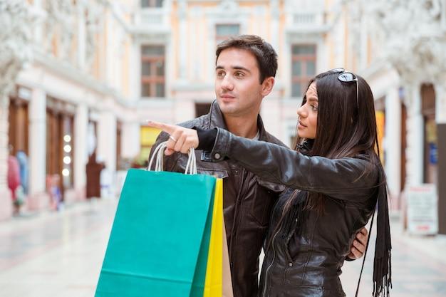 Портрет женщины с хозяйственной сумкой, указывая пальцем на что-то своему парню