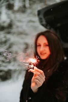 彼女の手に線香花火を持つ女性の肖像画
