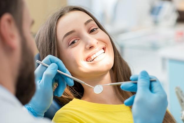 歯科医院での診察中に座っている歯を見せる笑顔の女性の肖像画