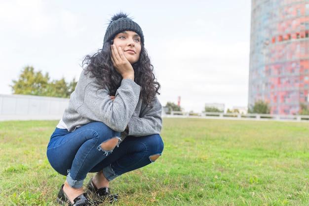 ウールキャップと公園でセーターを持つ女性の肖像画