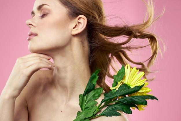 ピンクの背景に黄色い花を持つ女性の肖像画顔に化粧。高品質の写真