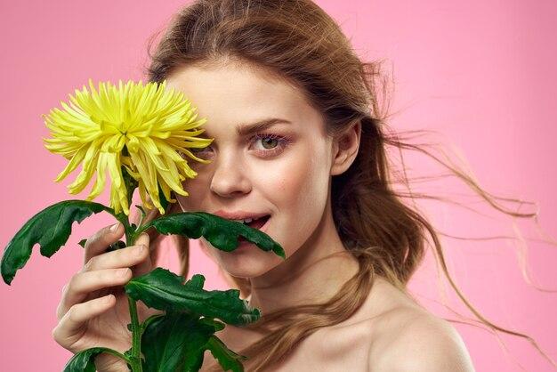 ピンクの背景に黄色い花を持つ女性の肖像画顔にメイク