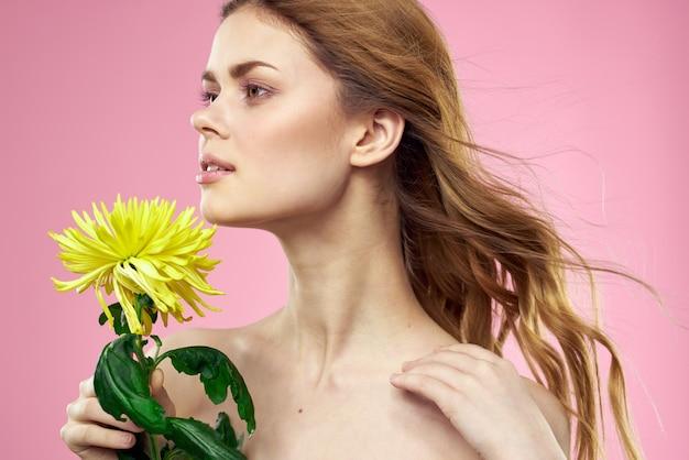 ピンクに黄色い花を持つ女性の肖像画