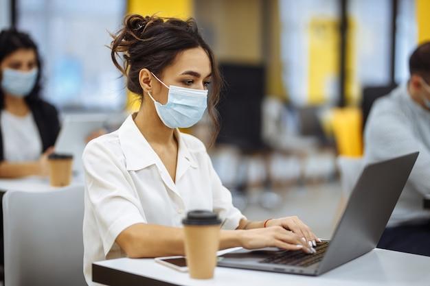 사무실 책상에서 랩톱으로 작업하고 의료 마스크를 착용하고 코로나 19 유행병 발생시 안전을 유지하는 여성의 초상화.