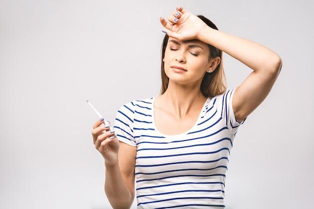 Портрет взволнованной молодой красивой женщины, проверяющей ее температуру