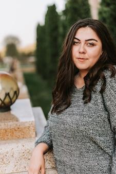 モダンな建物の背景に若い大人の女の子の肖像画