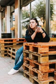 Портрет молодой взрослой девушки с чашкой кофе возле кафе в хорошую осеннюю погоду
