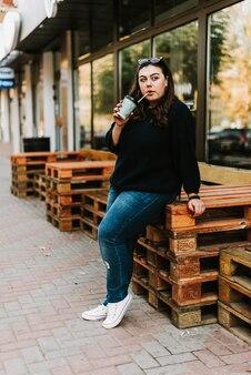 天気の良い秋のカフェの近くでコーヒーを飲みながら若い大人の女の子の肖像画