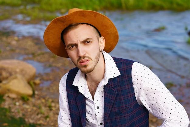 자연 경관을 배경으로 모자 흰 셔츠와 조끼를 입은 젊은 성인 남자의 초상화
