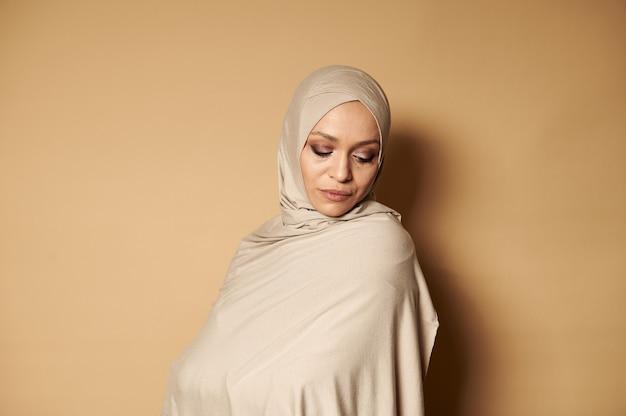 イスラム教徒の宗教的な衣装と覆われた頭を見下ろしている若い大人の女性の肖像画