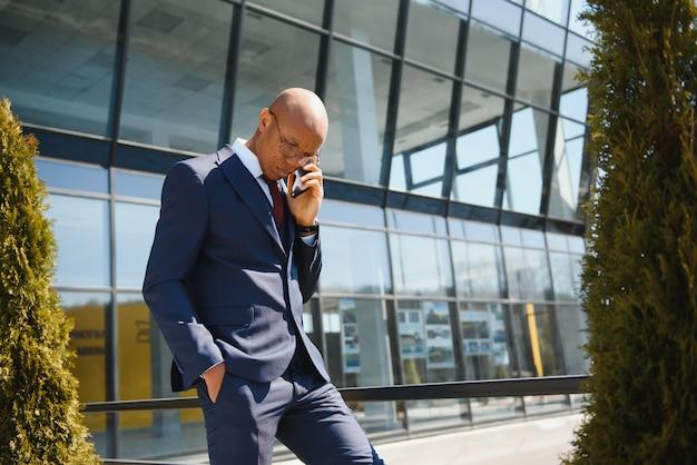 Портрет молодого афро-американского бизнесмена, разговаривающего по мобильному телефону на открытом воздухе в городе