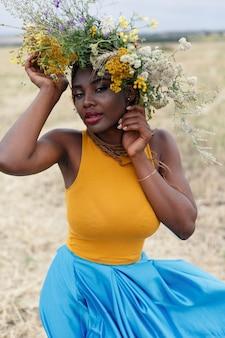 彼女の髪に大きな花を持つ、ファッションのモデル、若いアフリカ系アメリカ人の女性の肖像画。花のフィールドで曲がった計画の女の子の肖像画。彼女の頭に花輪