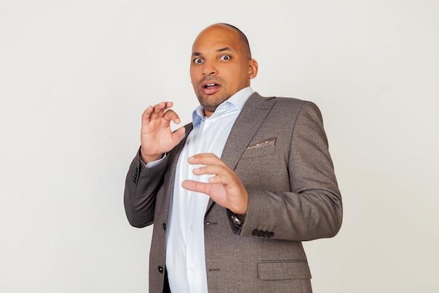 彼の顔に怯えた表情で叫んでいる若いアフリカ系アメリカ人の男のビジネスマンの肖像画。おびえた男は手で身を守る。否定的な感情