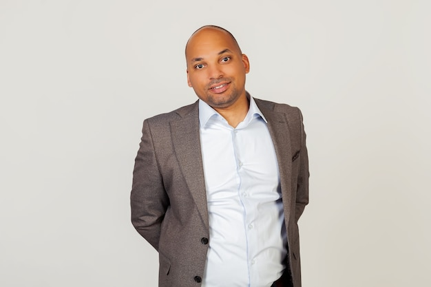 Портрет молодой афро-американский парень бизнесмен улыбается, позирует