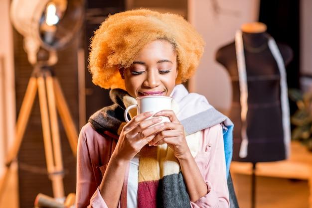 스튜디오 내부에서 뜨거운 음료를 들고 화려한 스카프를 두른 젊은 아프리카 창조적 인 사람의 초상화