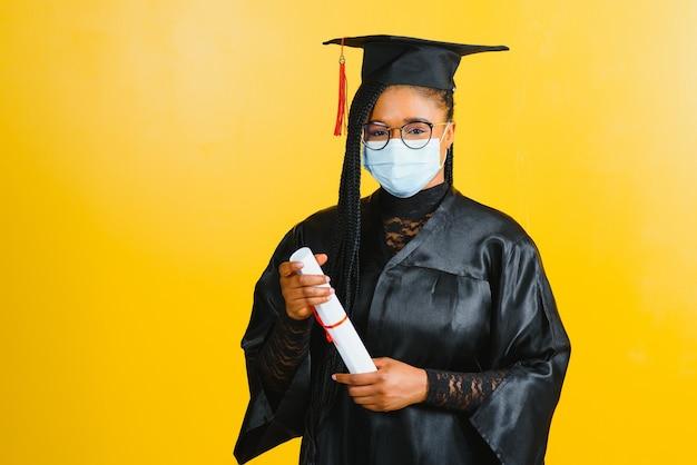 黄色の壁に、大学院キャップ保護マスクで若いアフリカの学生の肖像画、卒業2021