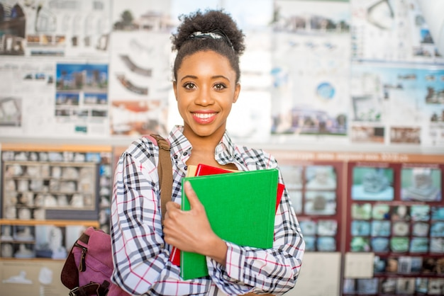 Портрет молодого африканского студента, стоящего с книгами перед дипломным проектом в университете