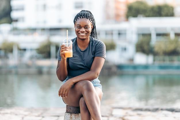 シェイクを保持し、屋外のカメラに笑みを浮かべて座っている若いアフリカの女性の肖像画