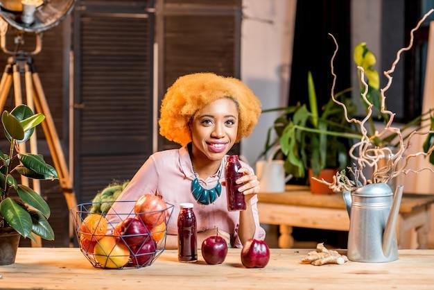 아늑한 집 내부에 앉아 신선한 붉은 과일과 스무디를 곁들인 젊은 아프리카 여성의 초상화