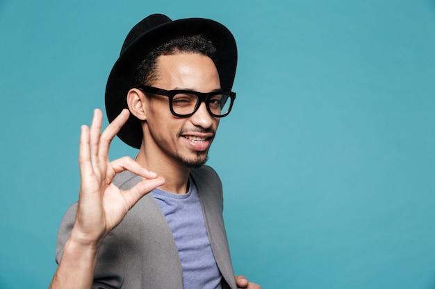帽子まばたきの若いアフロアメリカンの男の肖像