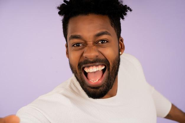 Портрет молодого афро-человека, смотрящего в камеру и улыбающегося, принимая селфи на изолированном фоне.